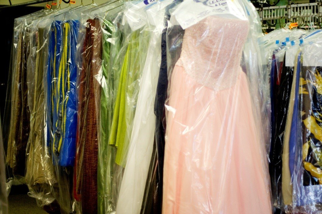 Several clothes and outfits stored in plastic garment bags to keep them clean and wrinkle-free