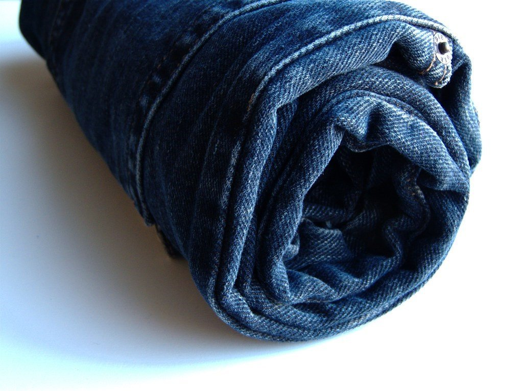A pair of jeans rolled to store and prevent wrinkles
