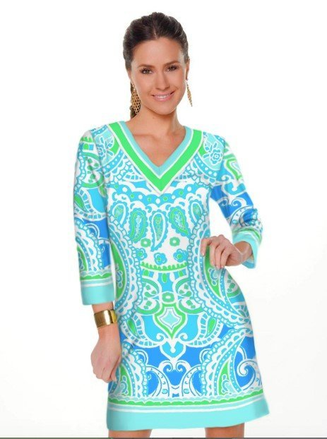 A model wears a tunic-style v-neck dress with gorgeous green and seafoam print.