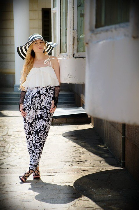 A woman wearing a stylish pair of palazzo Pants with a cropped top, hat, and heels