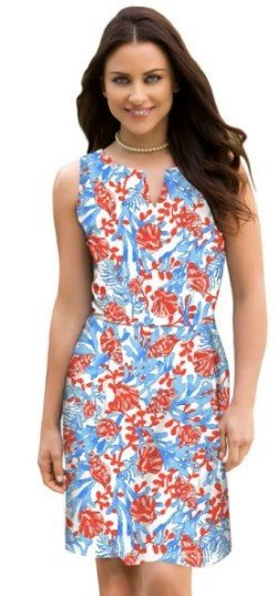 A woman posing in a casual, chic, red, blue, and white summer dress.
