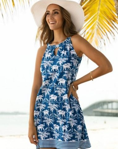 A woman wears a stylish printed dress and sun hat while at the beach on vacation.