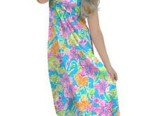 A woman poses in a beautiful flowy maxi dress that is great as maternity wear.