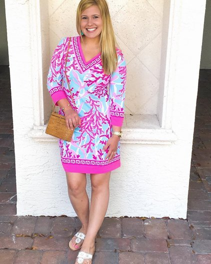 A woman poses in a loose, comfy tunic against a wall while on vacation.